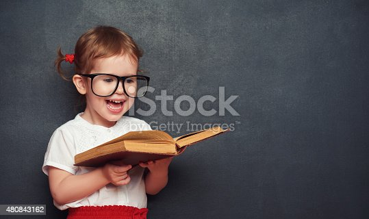 istock funny happy  girl schoolgirl with book from blackboard 480843162