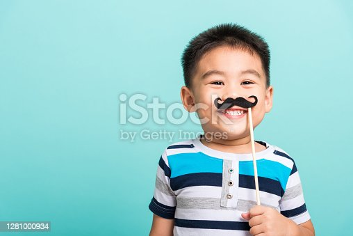 Funny happy hipster kid holding black mustache props for the photo booth close face, studio shot isolated on a blue background, Men health awareness, Prostate Cancer Awareness