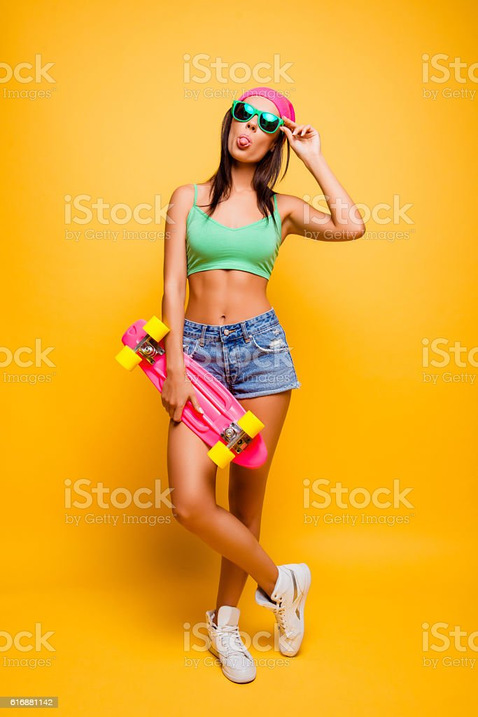 Cтоковое фото funny hipster girl showing tongue with pink longboard