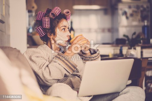 istock Funny housewife at home with pink curlers drinking a cup of tea while use a laptop on the sofa - technology and daily lifestyle at home - vintage filter colors and middle age lady enjoying the indoor leisure activity 1144083030