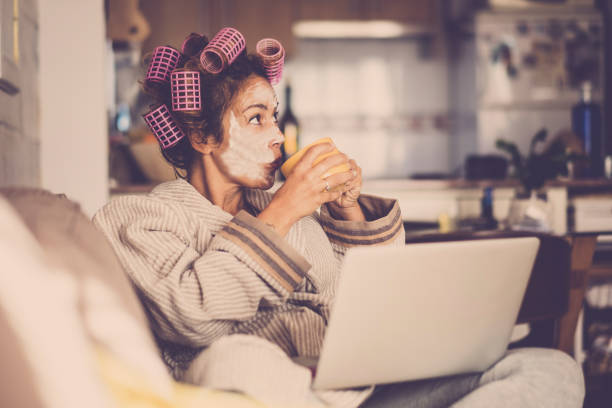 Funny housewife at home with pink curlers drinking a cup of tea while use a laptop on the sofa - technology and daily lifestyle at home - vintage filter colors and middle age lady enjoying the indoor leisure activity stock photo