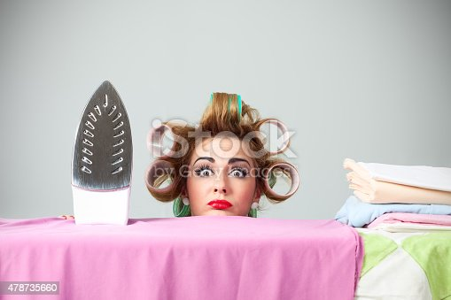Studio portrait of funny stereotypical housewife hiding behind ironing board. Nerdy wife with curlers in hair is making confused and surprised face. Behind her is gray background. She is looking to camera.