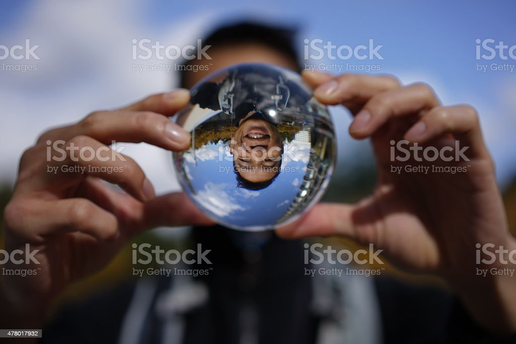 Funny image of asian man through a crystal ball stock photo