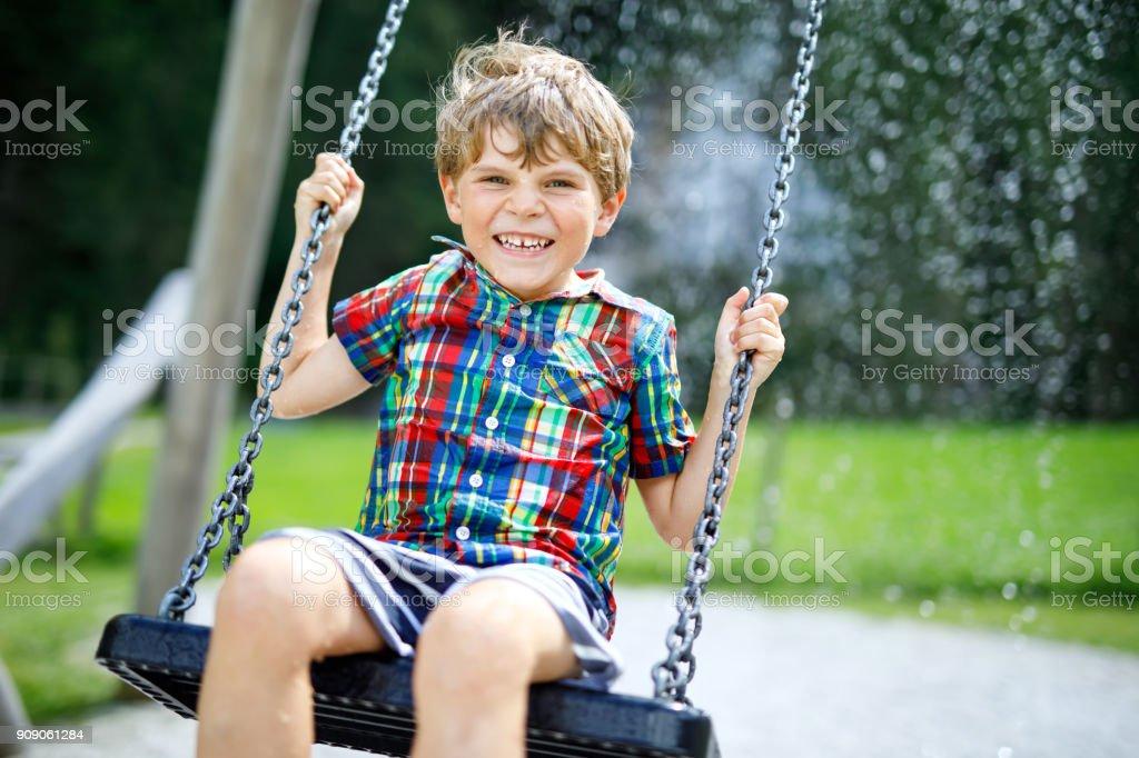 Lustiges Kind junge Spaß mit Kette Schaukel auf dem Spielplatz im Freien bei Regen – Foto