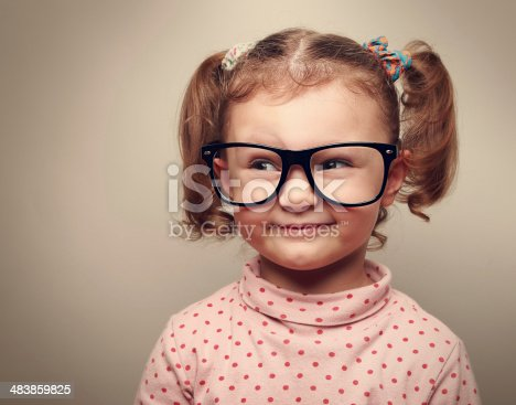 istock Funny kid girl in glasses looking on empty copy space 483859825
