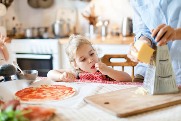 Funny kid gourmet is eating and tasting cheese. Family are cooking pizza in kitchen. Mother and daughter are preparing homemade italian food. Little girl is helping woman. Children chef concept. stock photo