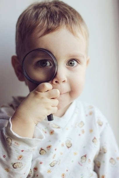 funny kid holding a magnifying glass near the eye stock photo