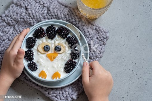 Funny kids breakfast coconut rice porridge with fresh berries