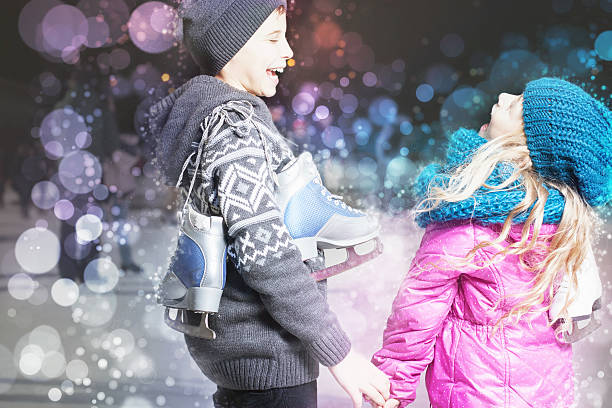 Funny kids holding ice skates shoes at ice rink outdoor Funny kids holding ice skates shoes at ice rink outdoor, sport and healthy lifestyle ice skating at Holland, Europe, night. Cute children, boy and girl laughting ice skating stock pictures, royalty-free photos & images