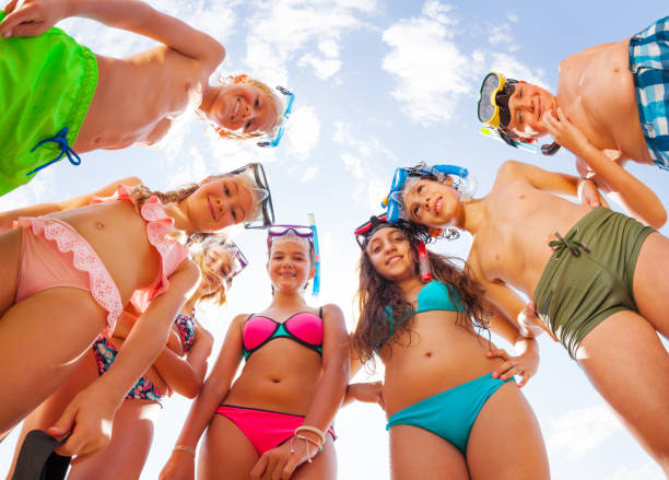 Funny kids in swimsuit bending looking from above stock photo