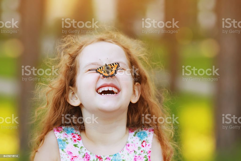 Funny laughing curly girl with a butterfly on his nose. - foto stock