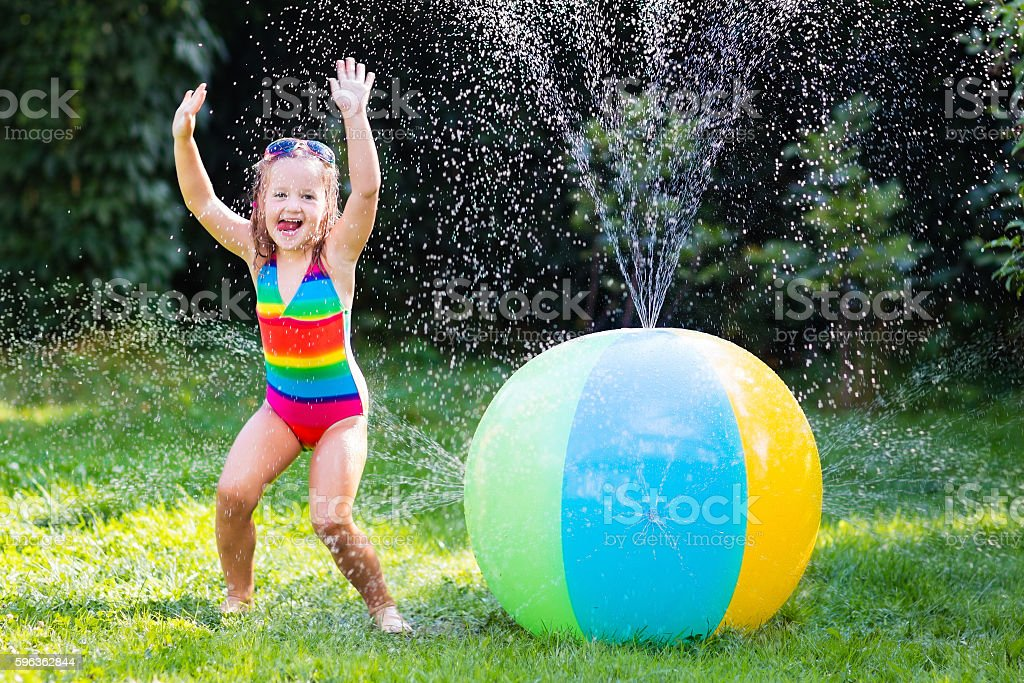 Funny laughing little girl playing with toy ball garden sprinkler royalty-free stock photo