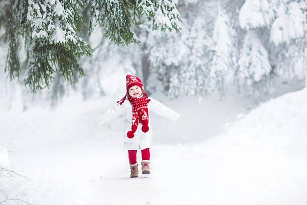 lustiger lachen mädchen laufen in einer schönen verschneiten park - festliche babymode junge stock-fotos und bilder