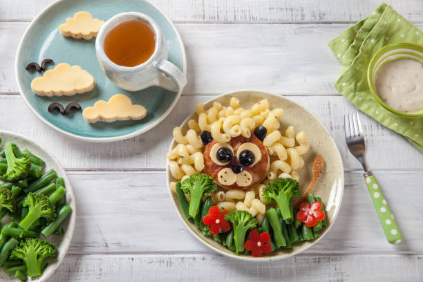 lustiger löwe essen gesicht mit schnitzel, nudeln und gemüse - gesunde huhn pasta stock-fotos und bilder