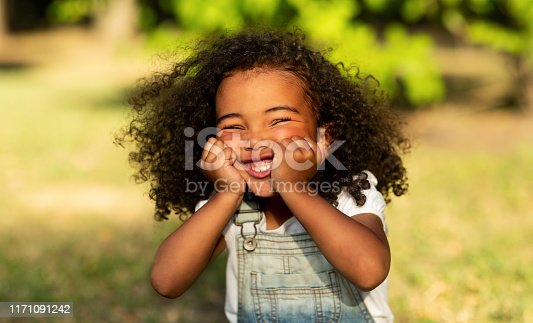 Funny little afro girl touching cheeks and having fun in nature park