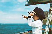 Funny baby captain on board of sailing yacht watching offshore sea on summer cruise. Travel adventure, yachting with child on family vacation. Kid clothing in sailor vintage style, nautical fashion