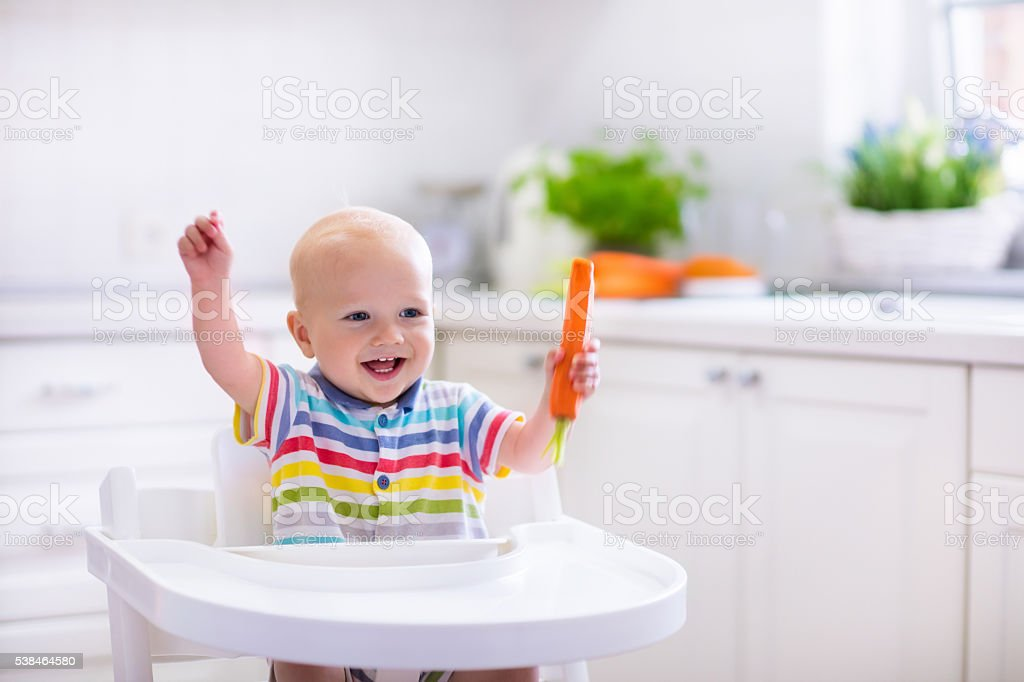 Funny little baby eating carrot stock photo