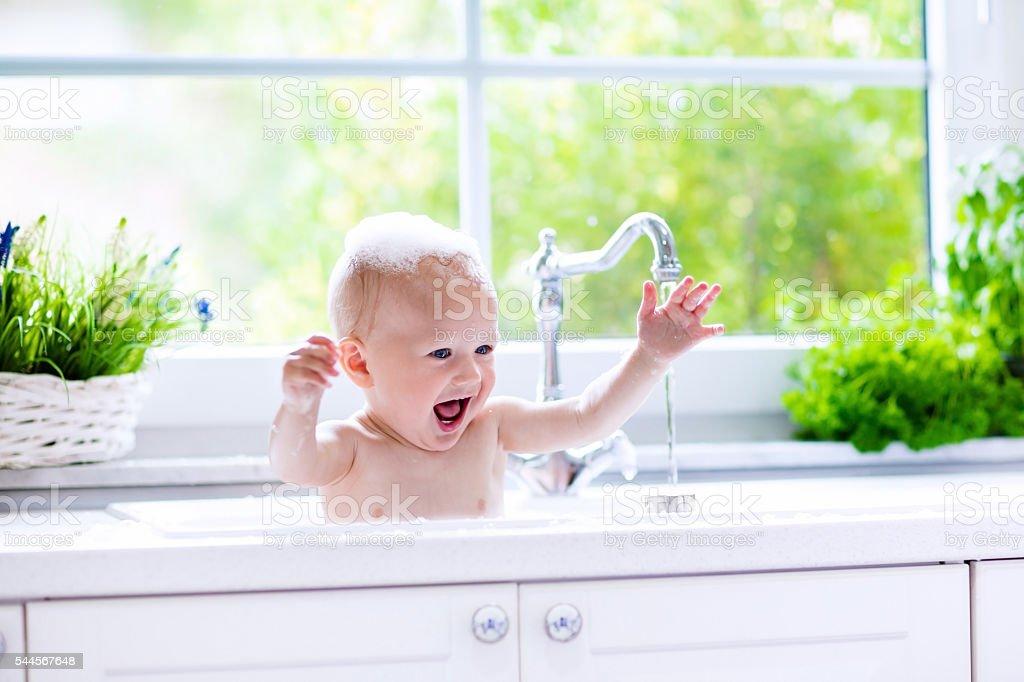 Funny little baby taking bath stock photo
