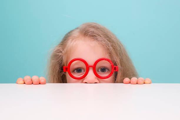 Funny little blonde girl with glasses looking at the camera. stock photo