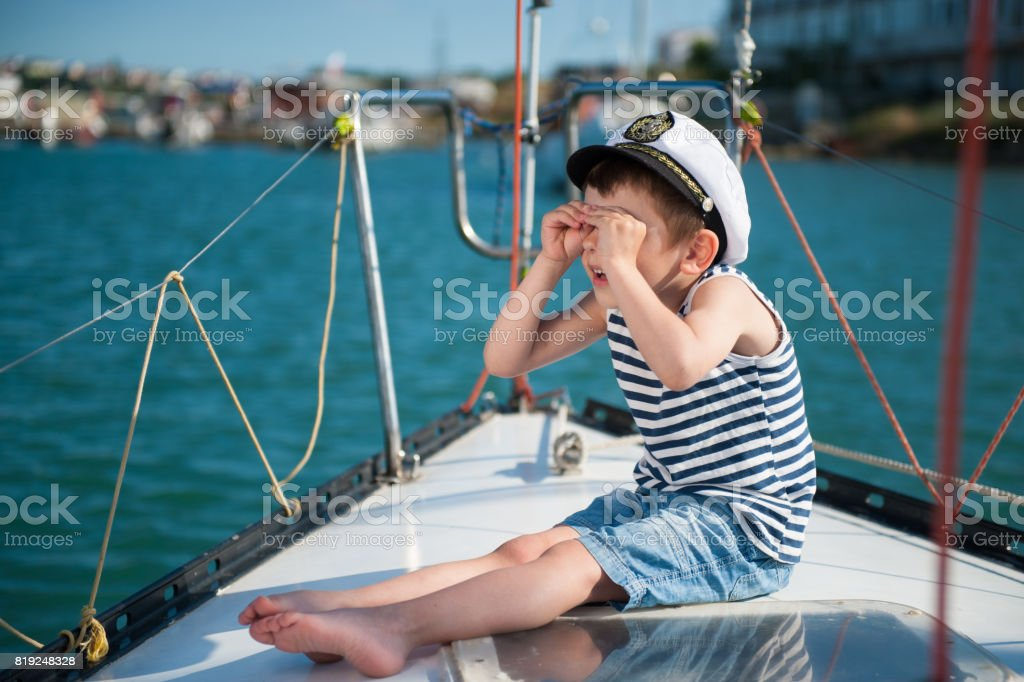 Funny little boy captain on a yacht in the summer stock photo