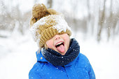 istock Funny little boy in blue winter clothes walks during a snowfall. Outdoors winter activities for kids. 1277114647