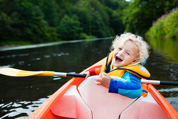 Funny little boy in kayak Happy kid enjoying kayak ride on beautiful river. Little curly toddler boy kayaking on hot summer day. Water sport and camping fun. Canoe for children. Funny child with vessel in a boat. wading stock pictures, royalty-free photos & images