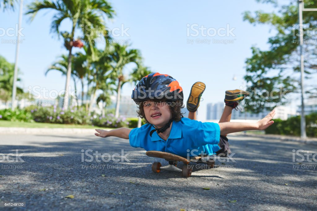 Funny little boy on skateboard stock photo