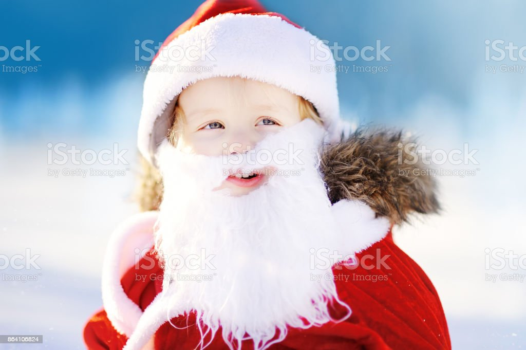 Funny little boy wearing Santa Claus costume in winter snowy park royalty-free stock photo