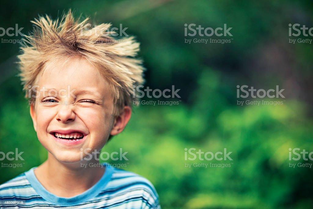 Funny little boy winking stock photo