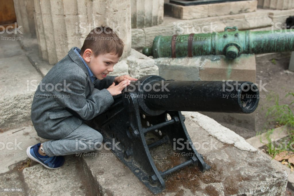 funny little boy with an old little gun stock photo