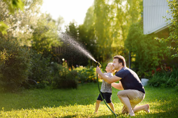 Funny little boy with his father playing with garden hose in sunny backyard Funny little boy with his father playing with garden hose in sunny backyard. Preschooler child having fun with spray of water. Summer outdoors activity for kids. lawn stock pictures, royalty-free photos & images