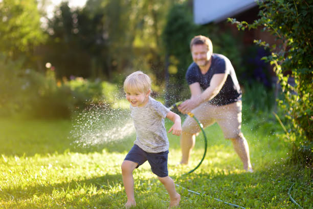 Funny little boy with his father playing with garden hose in sunny backyard. Preschooler child having fun with spray of water. stock photo