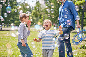 Portrait shot of cute little boy trying to catch soap bubbles with his mouth while having childrens party at green public park illuminated with sunbeams