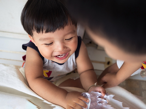 istock Funny little boys enjoy playing a piece paper together 840592516