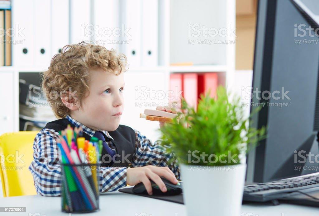 Lustige Kleine Kaukasischen Junge Isst Eine Sandwich Mit Wurst Am Arbeitsplatz Im Buro Und Dem Computerbildschirm Betrachten Stockfoto Und Mehr Bilder Von Anzug Istock