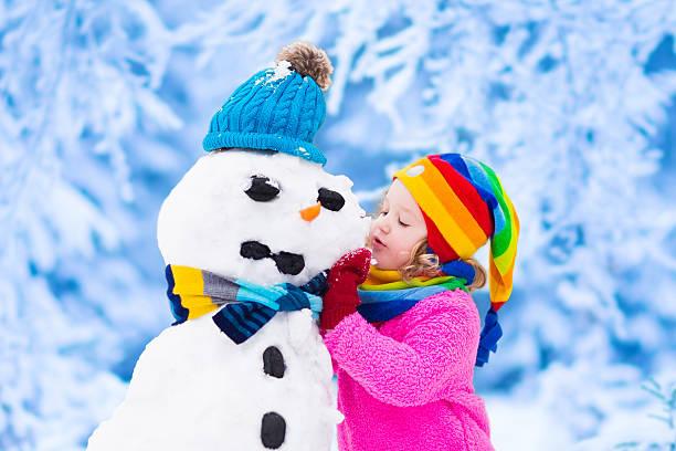 funny little girl building a snow man in winter - schneemann bauen stock-fotos und bilder