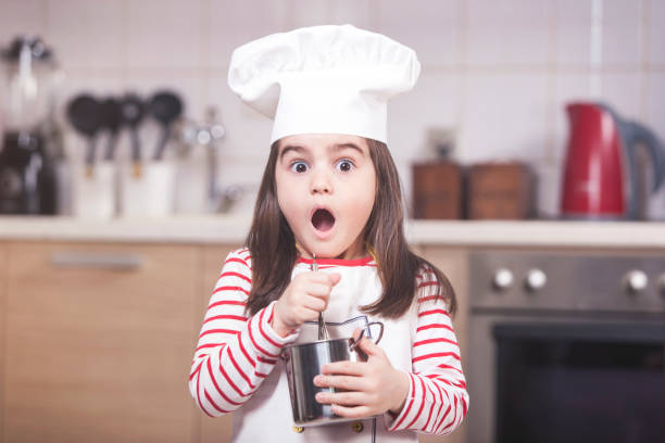 Funny little girl chef stock photo