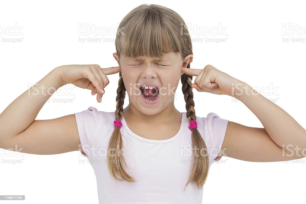 Funny little girl clogging her ears and wincing stock photo