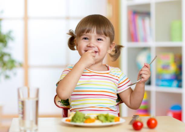 Funny little girl eating healthy food in kindergarten stock photo