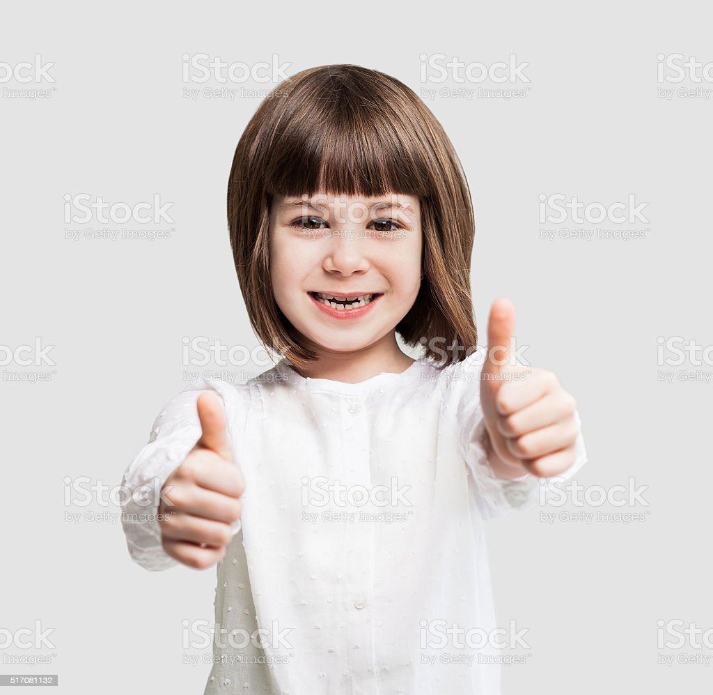 Funny little girl giving thumbs up stock photo
