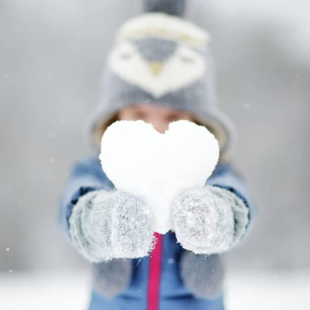 lustige kleine mädchen, die spaß in winter park - schneespiele stock-fotos und bilder
