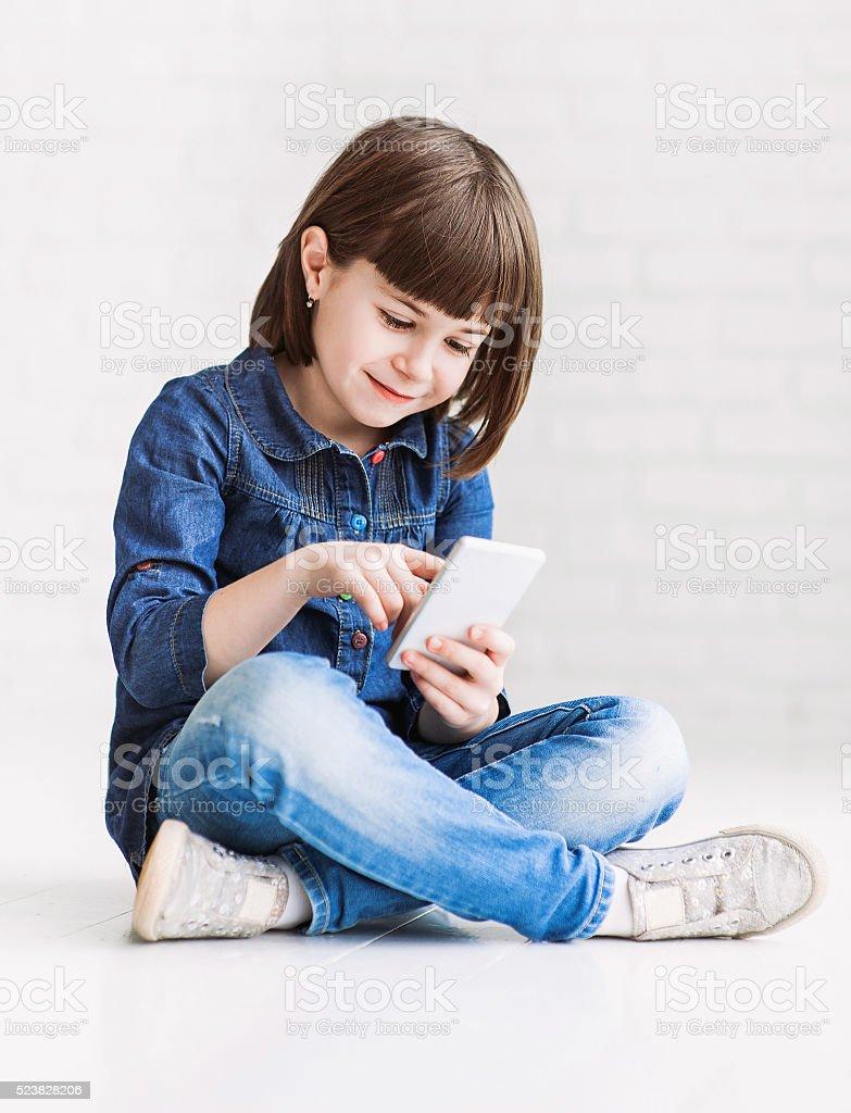 Funny little girl holding smart phone stock photo