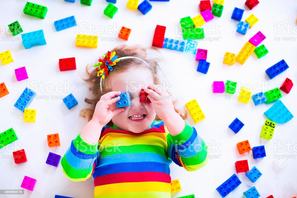 Funny little girl playing with colorful toy blocks stock photo