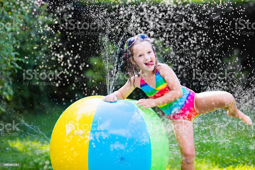 Funny little girl playing with toy ball garden sprinkler royalty-free stock photo