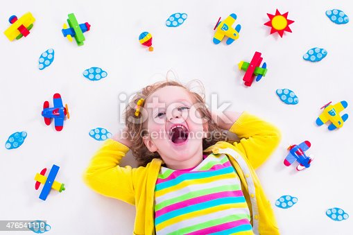 istock Funny little girl playing with wooden airplane 476541110