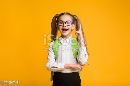 1176772377 istock photo Funny Little Girl Pointing Finger Up On Yellow Studio Background 1171094749