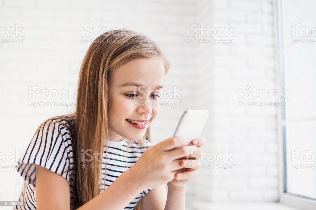 Divertido niña pequeña usando teléfono inteligente - foto de stock