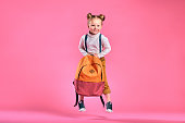 Funny little girl with big backpack jumping and having fun against pink wall. School concept. Back to School. School's out for summer. Celebrating the end of another successful school year. Copy space
