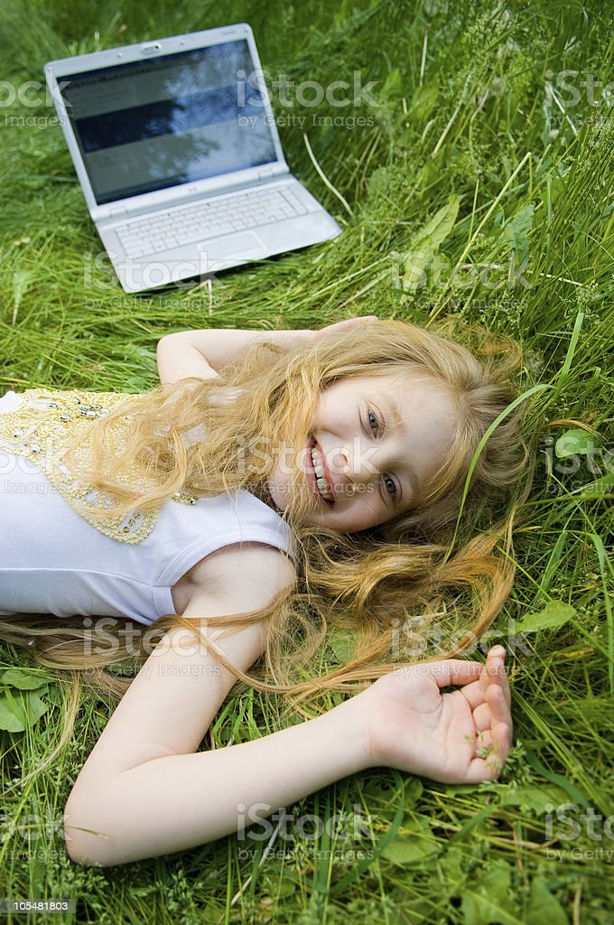 Funny little girl with laptop outside royalty-free stock photo
