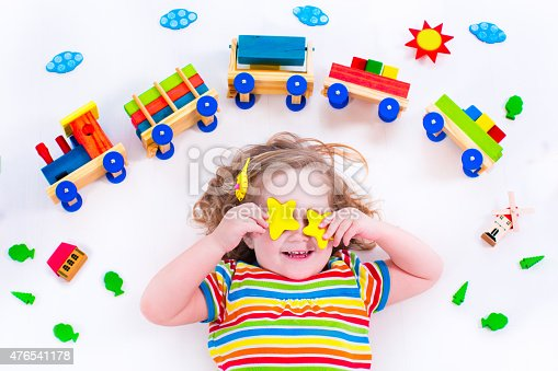 istock Funny little girl with wooden train 476541178